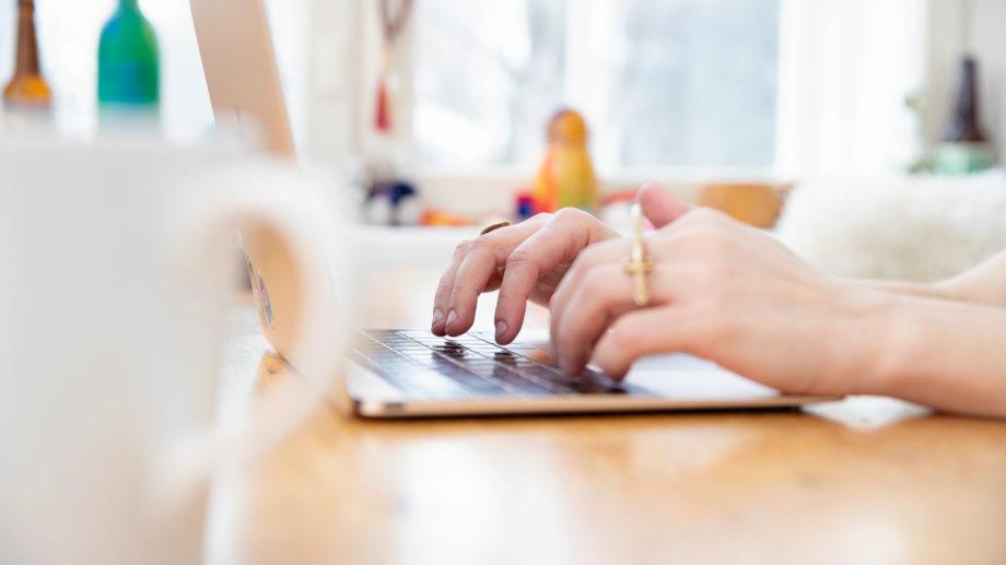 Puupöytä, jossa tietokone. Nainen kirjoittaa koneella asuntohakemusta. Taustalla ikkuna ja sisustusesineitä. Vasemmassa reunassa etualalla valkoinen kahvikuppi.