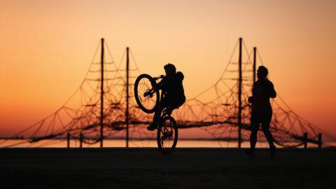 Poika temppuilee pyörällä, äiti lenkkeilee vieressä. Taustalla upea auringonlasku.