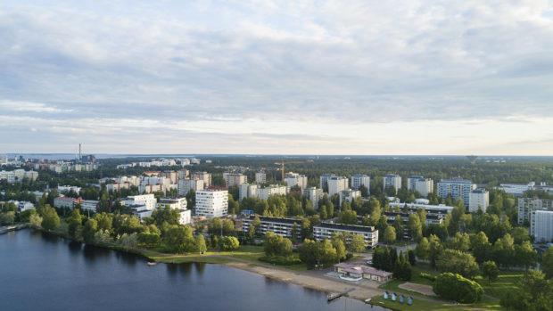 Lintuperspektiivistä oululaista kaupunkimaisemaa. Tuiran perinteinen uimaranta näkyy edustalla ja taustalla kerrostaloja. Kesäilta ja auringonlasku.