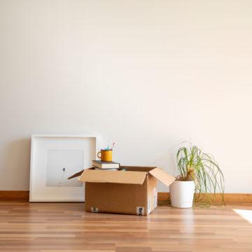 Vuokra-asunnon parkettilattialla muuttoa varten pakattuja tavaroita valmiina kannettavaksi.