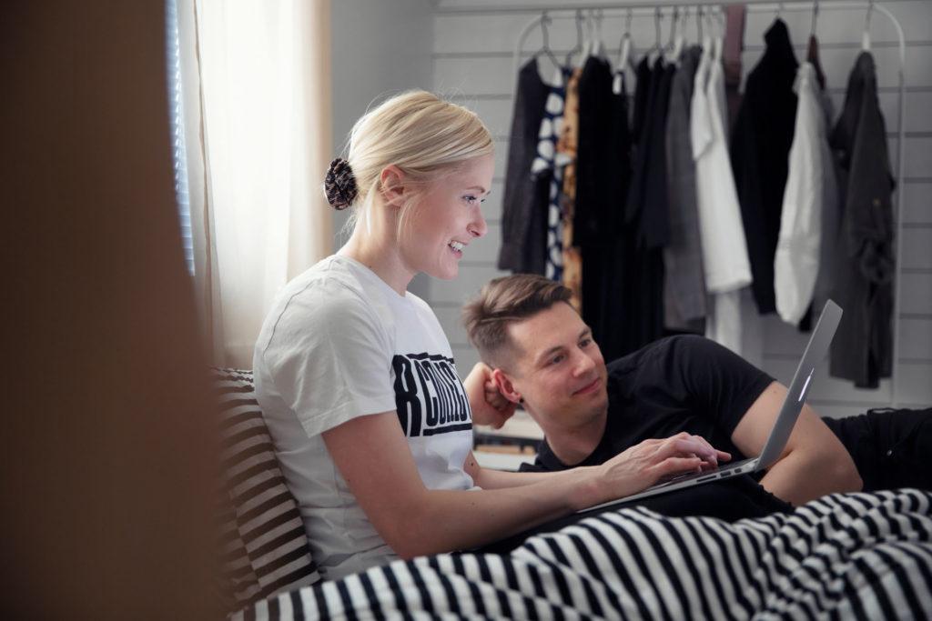 Hyväntuulinen pariskunta vuokra-asunnossa. Nainen kirjoittaa tohkeissaan kannettavalla tietokoneella. Käytössä on langaton verkkoyhteys. Sivakan asunnon vuokra sisältää usein internetyhteyden.