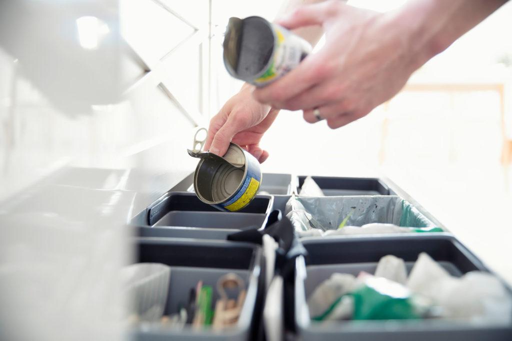 Vuokralainen lajittelemassa kotitalouden jätteitä oikeaoppisesti eri astioihin.