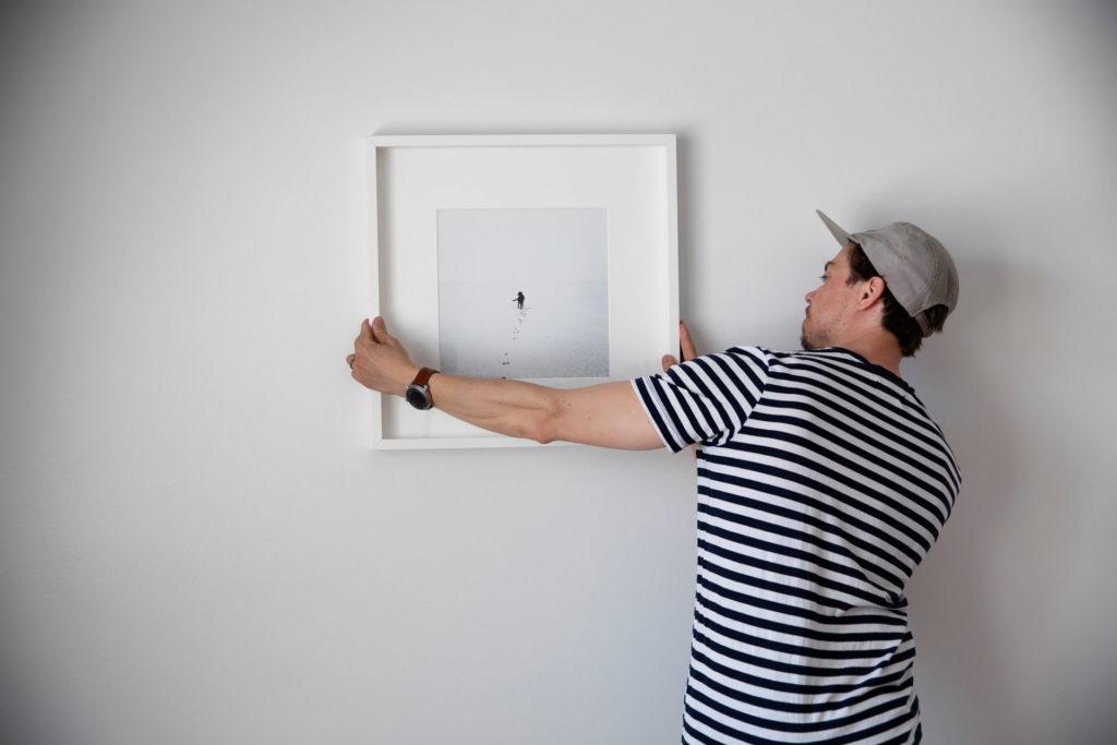 Nuori mies kiinnittää siististi taulua vuokra-asuntonsa seinään.