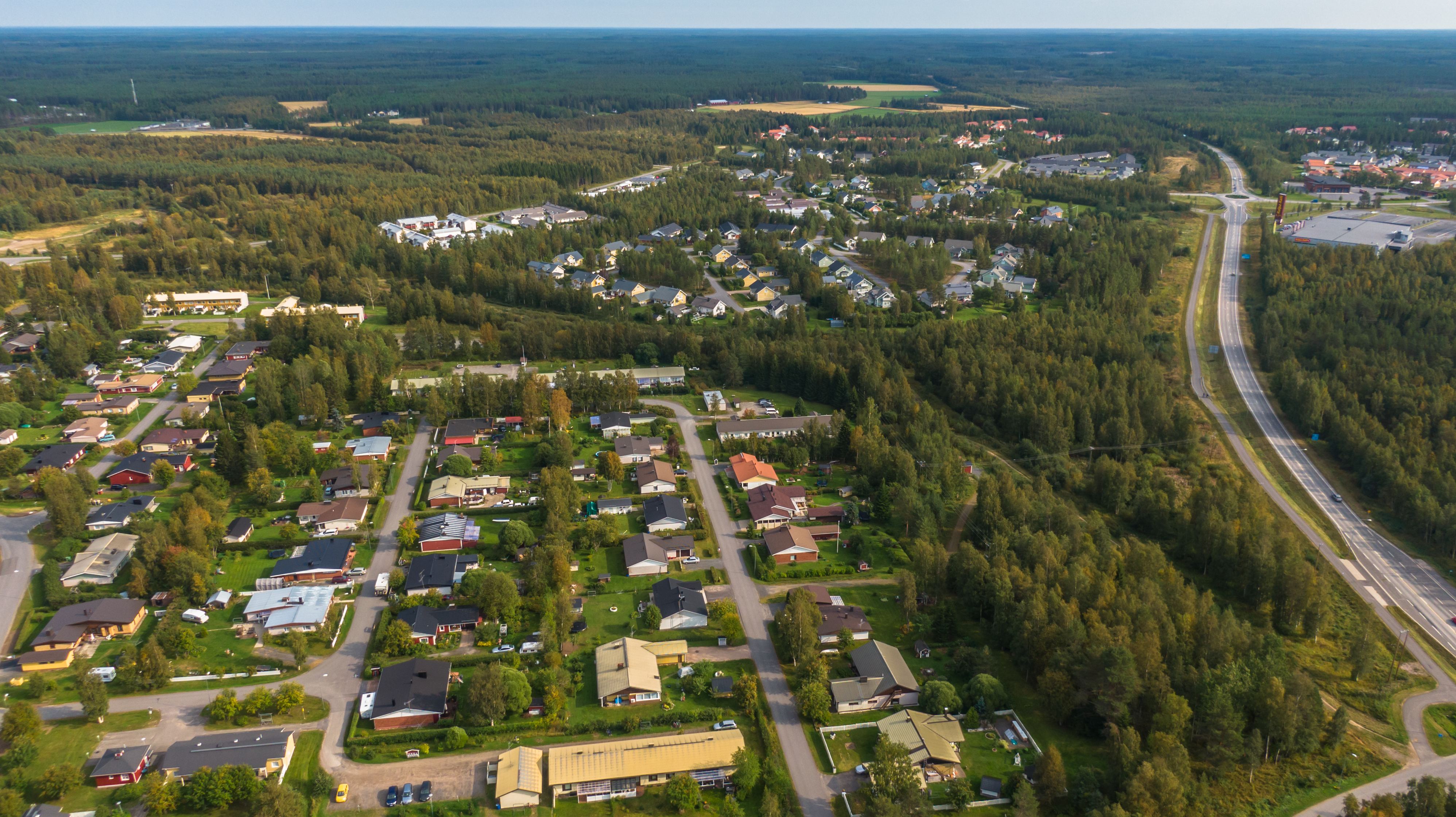 Lintuperspektiivistä otettu maisemakuva: Oulu, Haukipudas ja Haapakankaan rauhallinen asuinalue. Metsää, tieväyliä ja taloja.