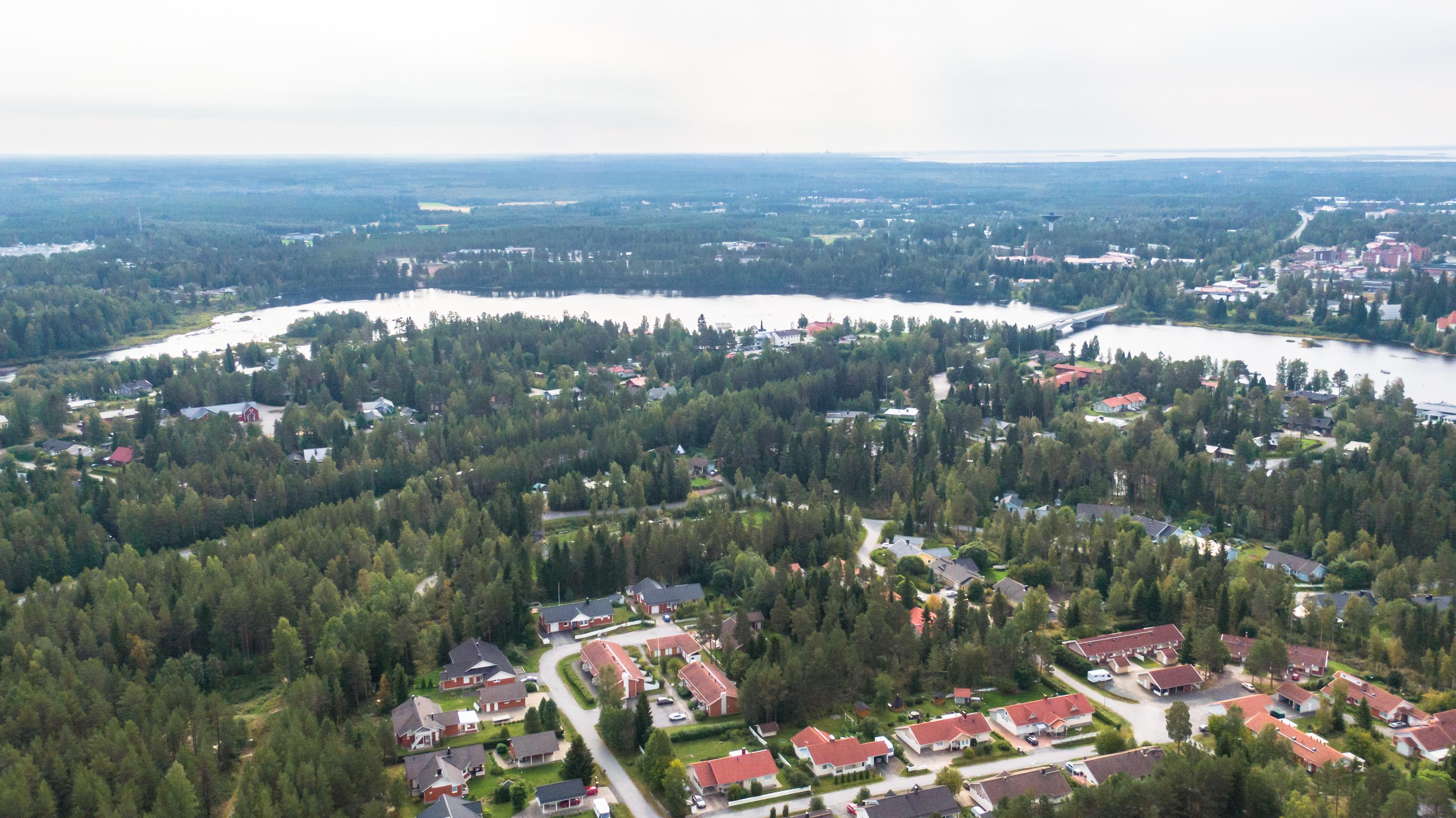 Ilmakuvassa on metsää, punakattoisia taloja ja yläosassa näkyy virtaavaa Kiiminkijokea.