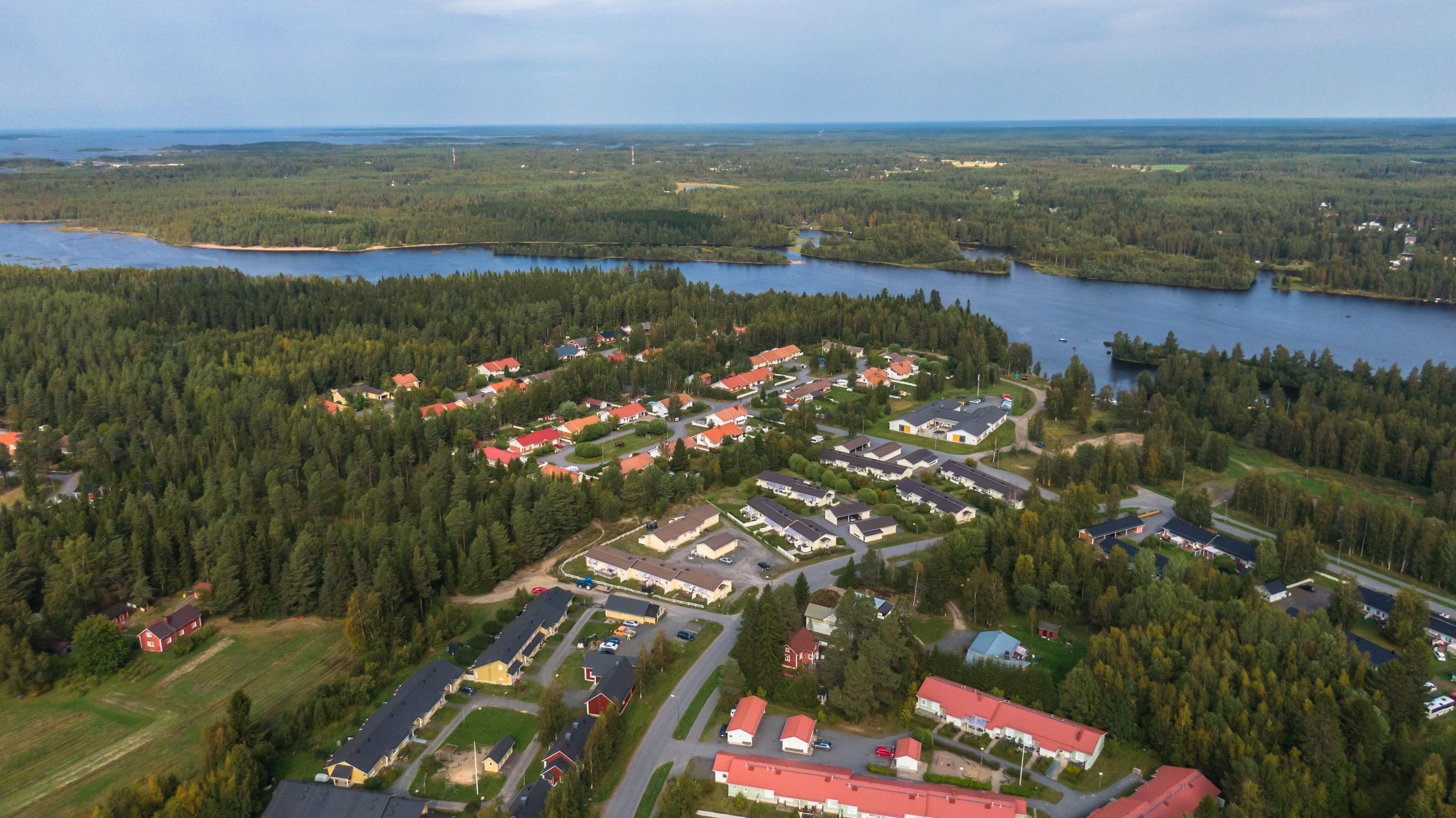 Metsäistä asuinaluetta ilmasta kuvattuna, jossa runsaasti punakattoisia taloja. Kuuluisa Kiiminkijoki taustalla.