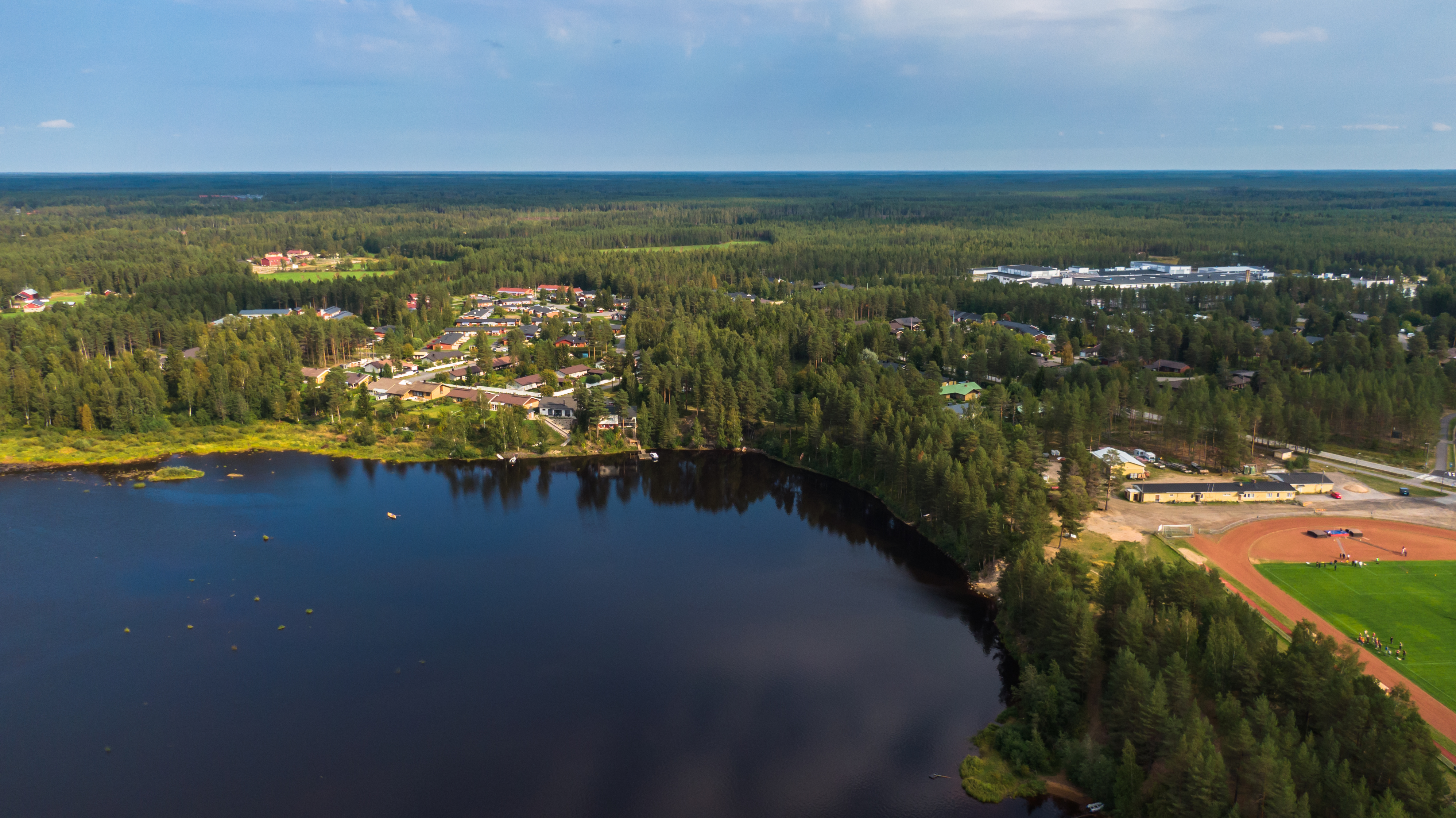 Ukonkaivoksen asuinaluetta ilmasta kuvattuna. Kiiminkijokea, metsäisiä maisemia ja urheilukenttä oikeassa reunassa.