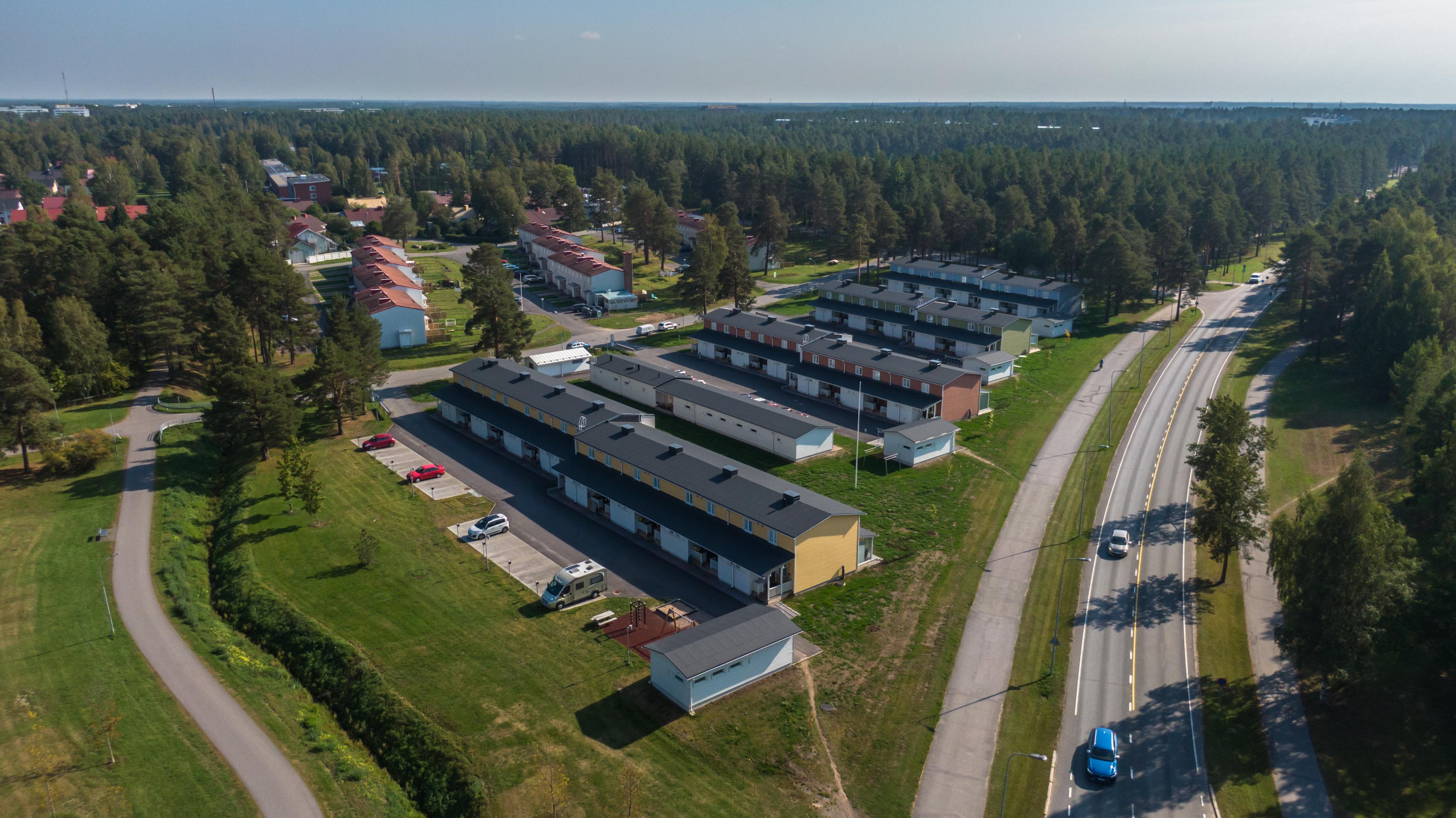 Oulun Höyhtyän kaupunginosaa ilmasta kuvattuna kesällä. Rivitaloja ja metsämaisemaa.