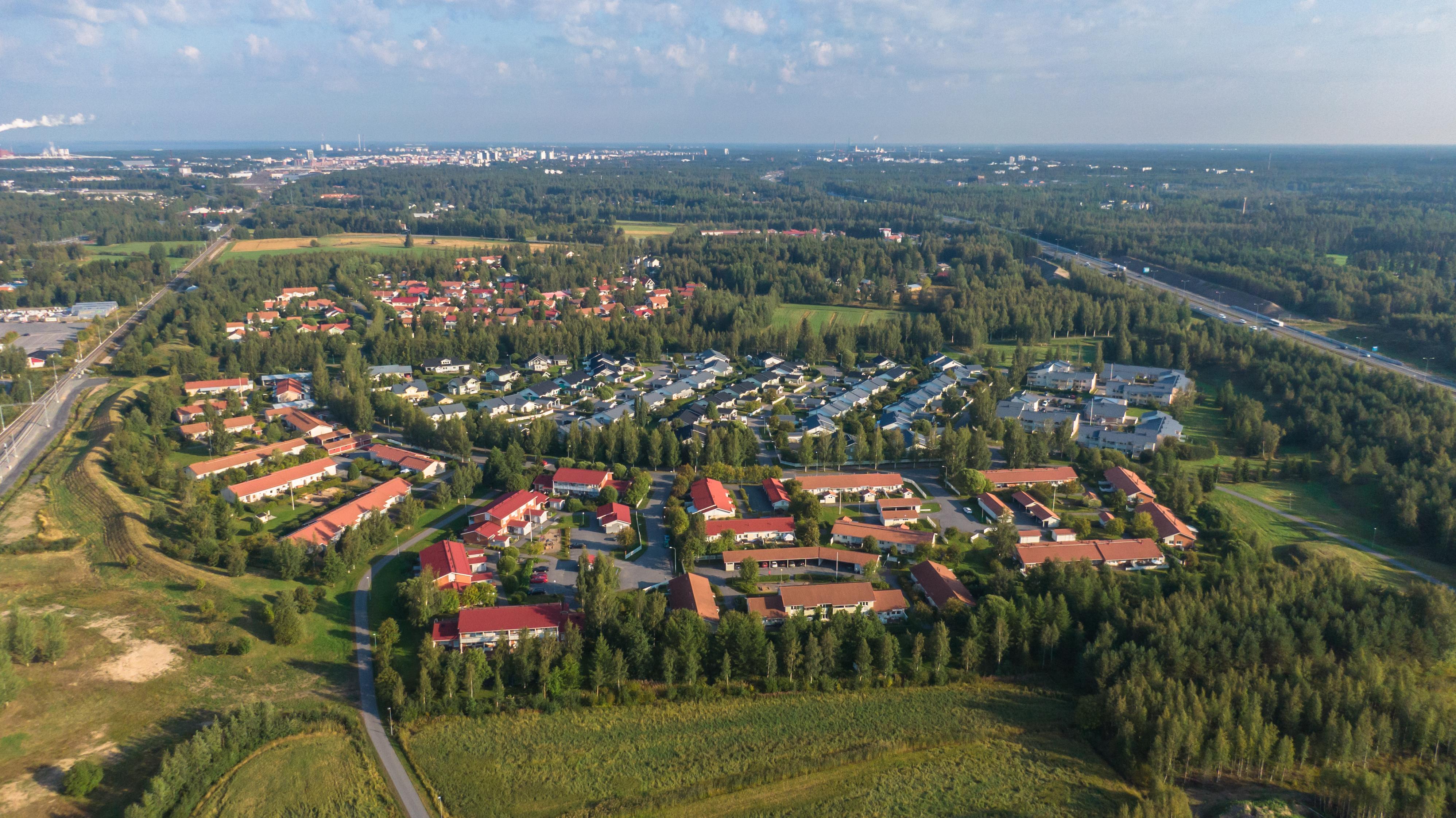 Ilmasta otettu kuva Oulun Kiviniemestä. Alueelta on viisi kilometriä keskustaan. Metsää, teitä ja erilaisia taloja.