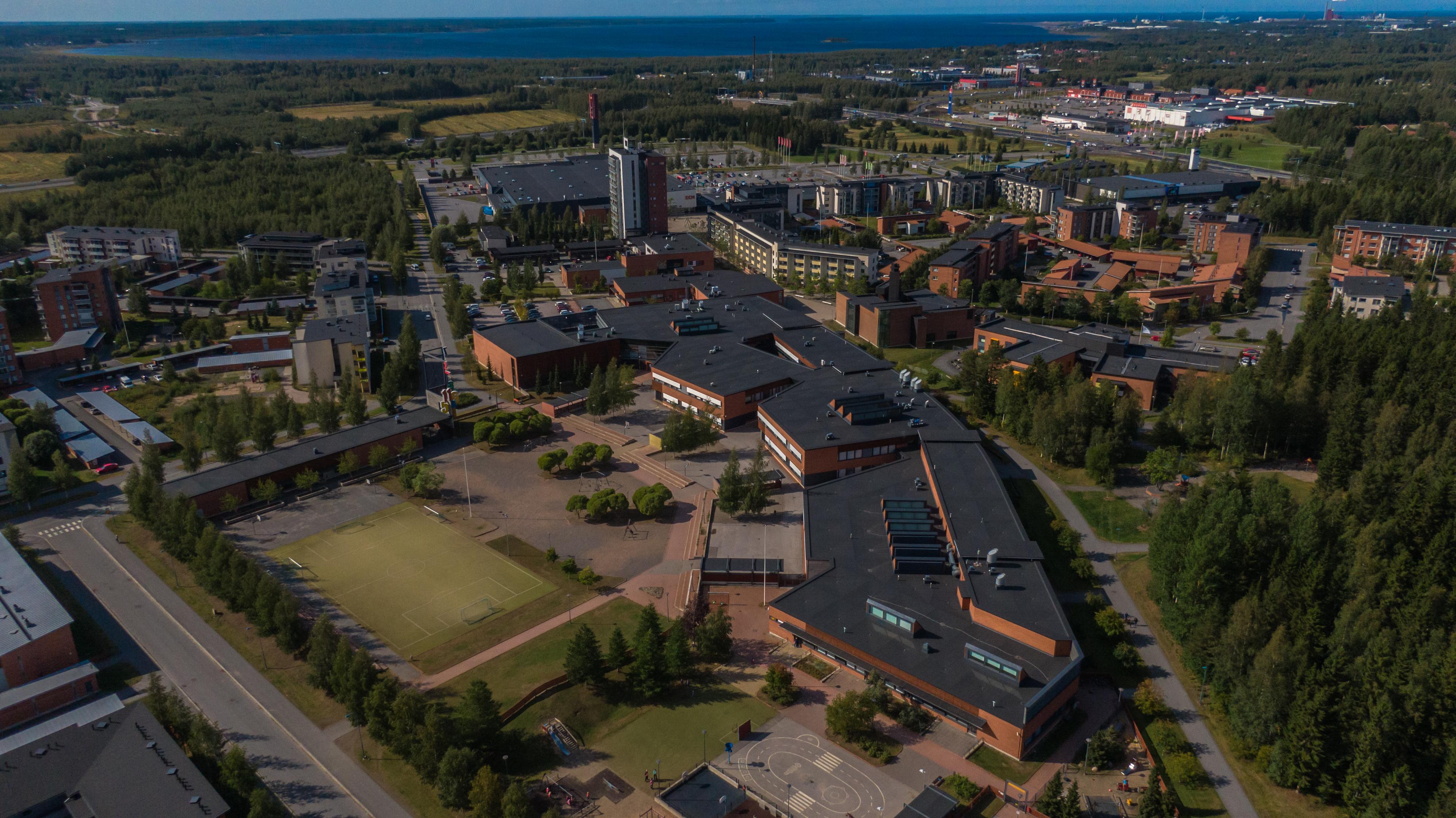 Korkealta otettu ilmakuva Kaakkurin keskustan tuntumasta. Kaakkurin koulu, pieni jalkapallokenttä ja punaisia sekä valkoisia kerrostaloja. Alueen korkein rakennus ja Pohjois-Suomen suurin päivittäistavaratalo taustalla.