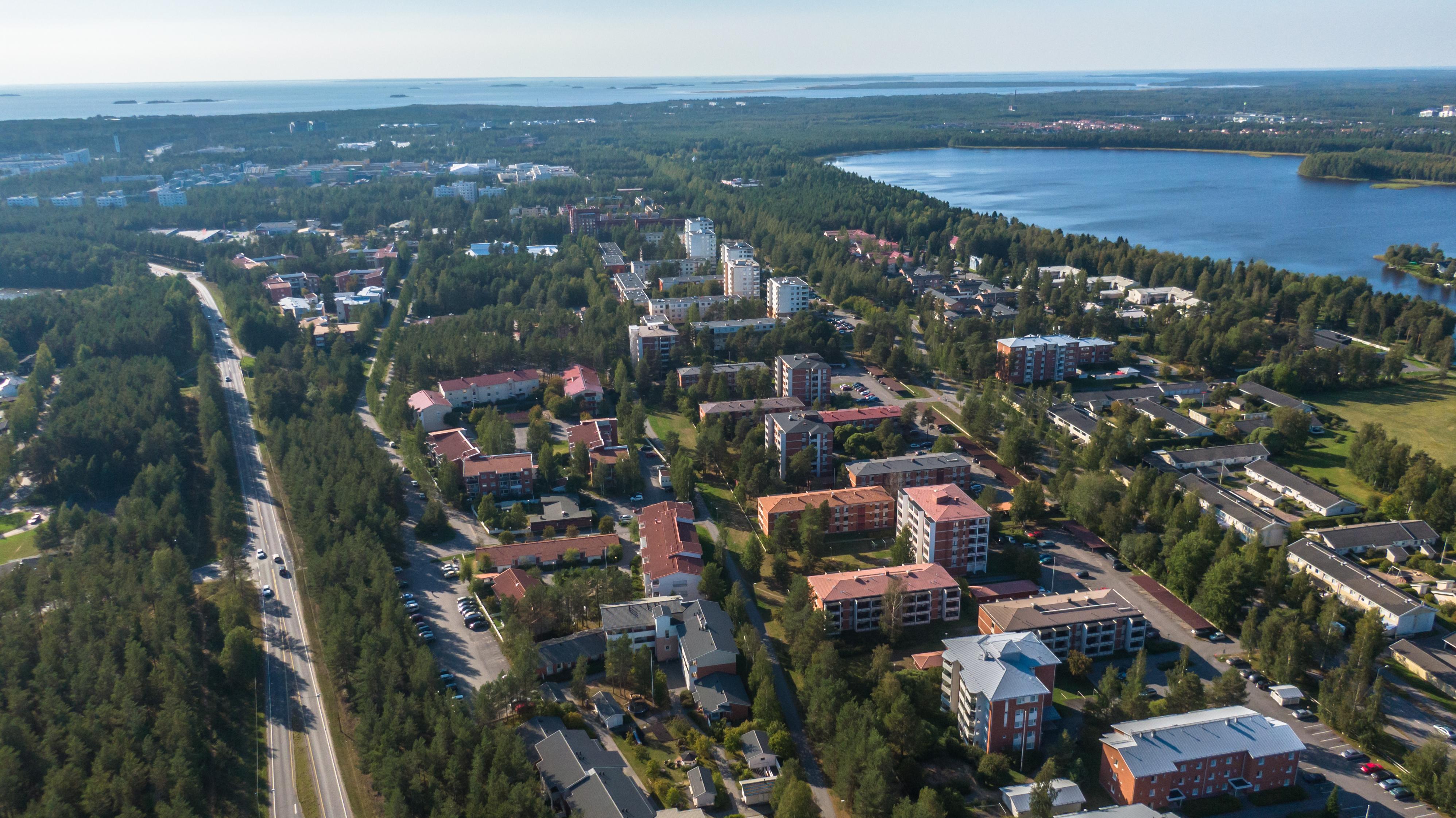 Ilmasta otettu kuva Oulun Kaijonharjun asuinalueelta. Metsää, kulkuväyliä ja kerrostalolähiötä. Kuivasjärvi on oikeassa yläkulmassa.