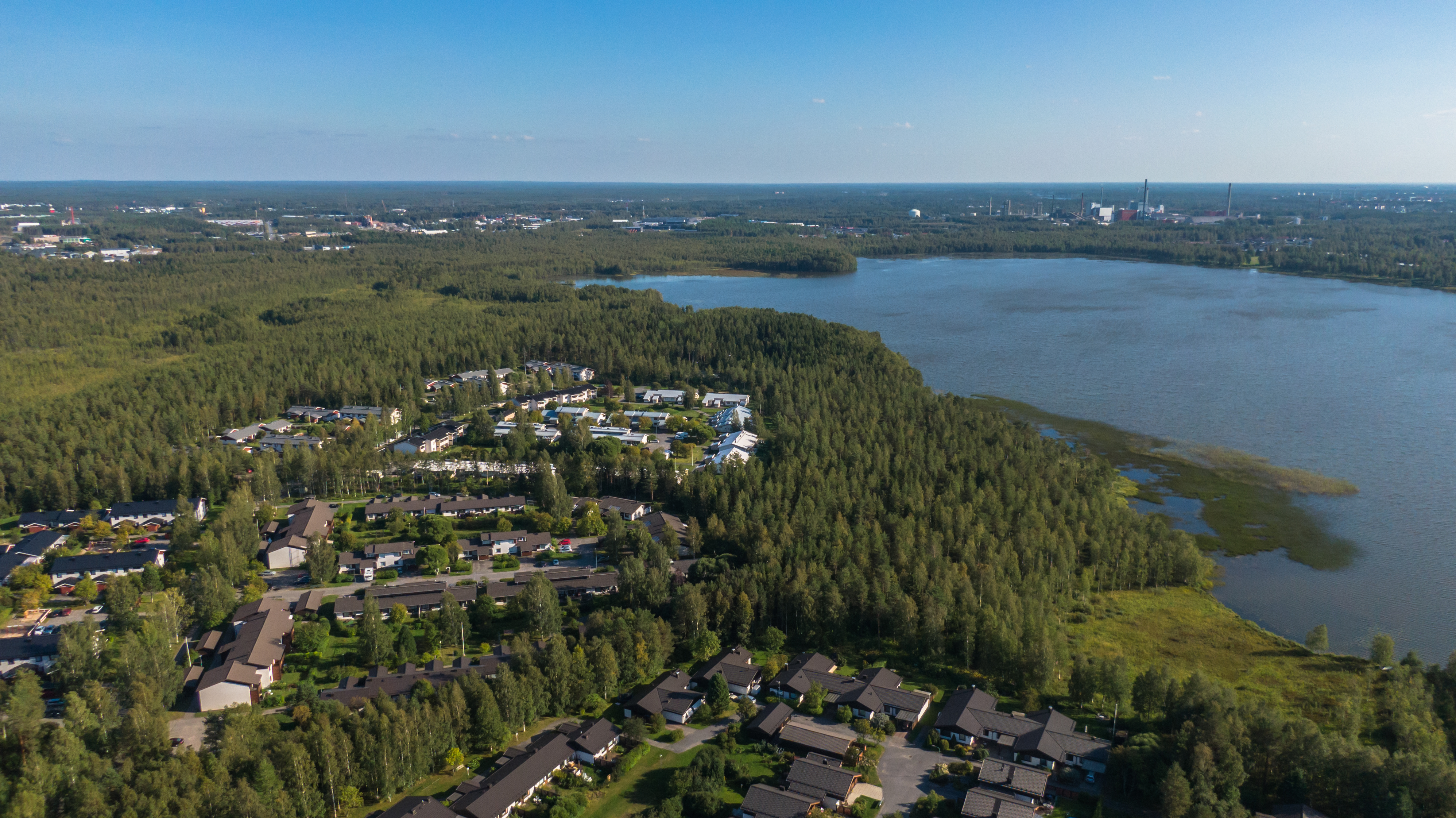 Dronella otettu ilmakuva Kaijonrannan asuinalueelta Oulusta. Pyykösjärvi ja kesäistä metsäistä maisemaaa. Melkein sininen taivas.