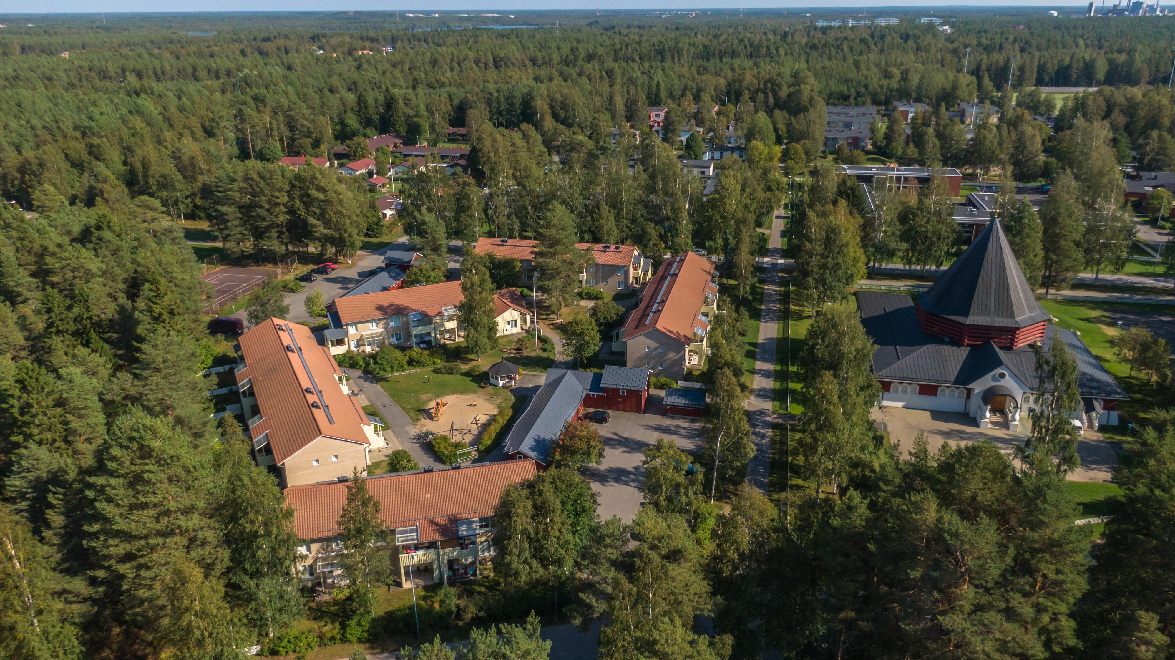 Metsän ympäröimää Koskelan asuinaluetta kesällä otetussa ilmakuvassa. Punakattoisia luhtitaloja ja kirkko oikeassa reunassa kirkko.