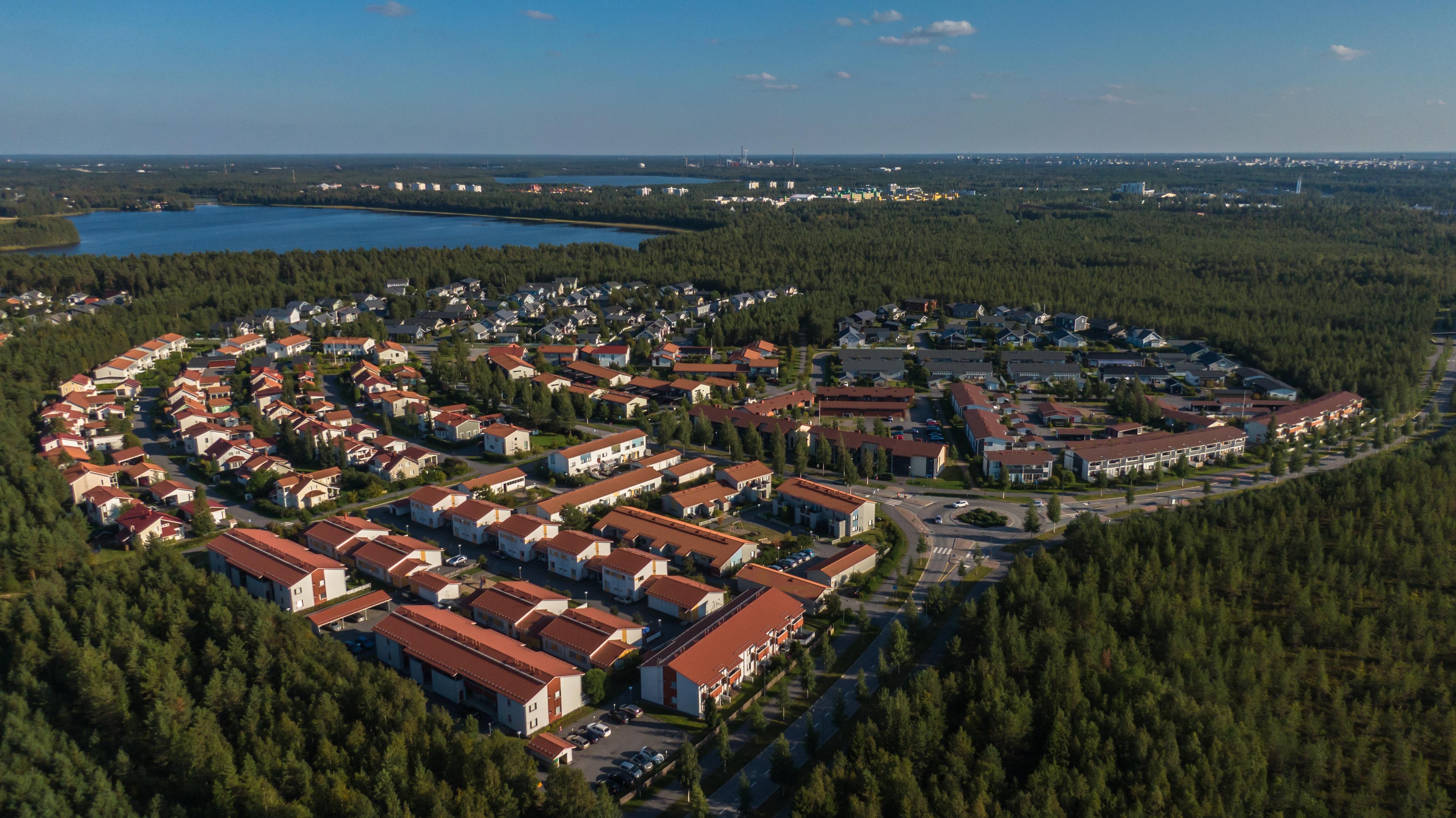 Oulun Kuivasrannasta otettu ilmakuva. Punakattoisia taloja ikään kuin puolikaaren muodossa. Ympärillä metsää, taustalla näkyy pieni Kuivasjärvi.
