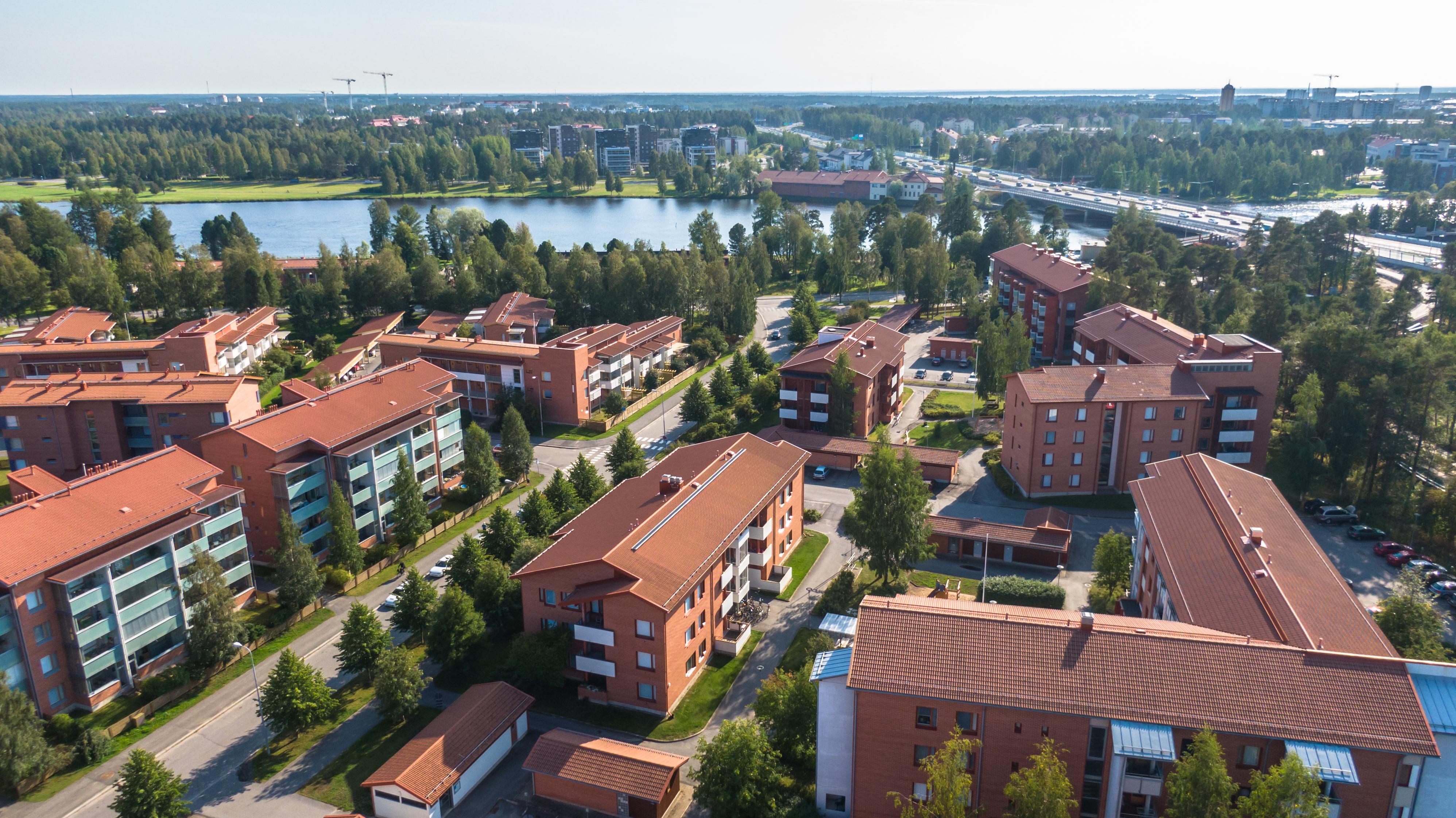 Oulun Laanilan asuinaluetta ilmasta kuvattuna. Kesäinen yleiskuva: tyylikkäitä kerrostaloja, taustalla joki, silta ja moottoritie.