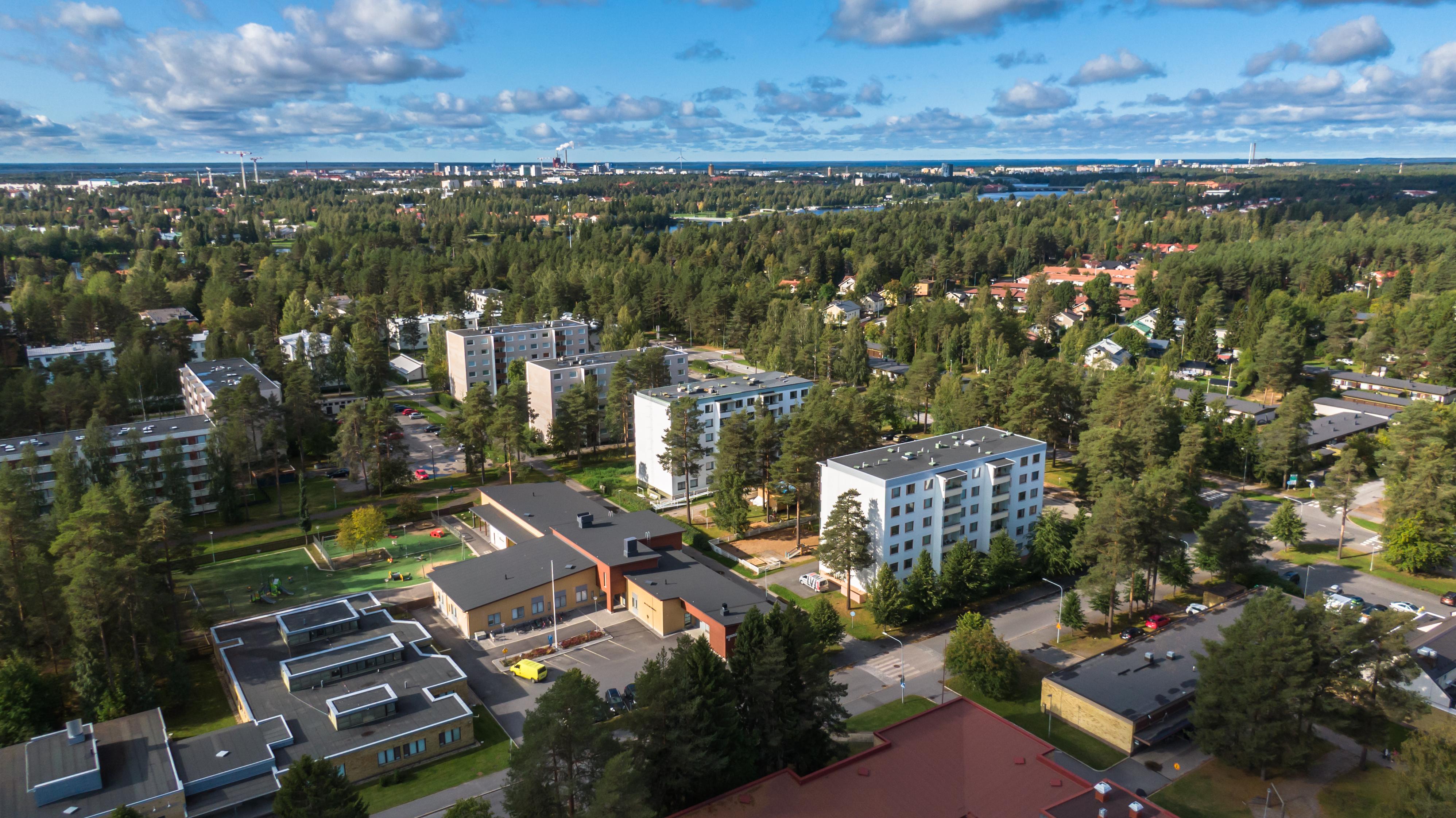 Ilmasta otettu kuva Oulun Myllyojan asuinalueesta. Valkoisia kerrostaloja kaupunkilähiössä.