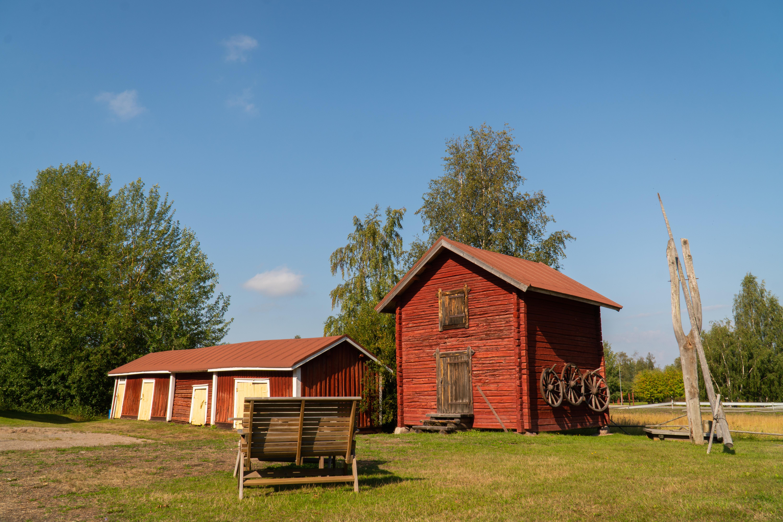 Historiallista vanhaa rakennuskantaa. Punainen puinen vanha aitta ja puuliiteri/vaja. Kesä ja peltomaisema. Puita, vihreää nurmea ja sinisen taivas.