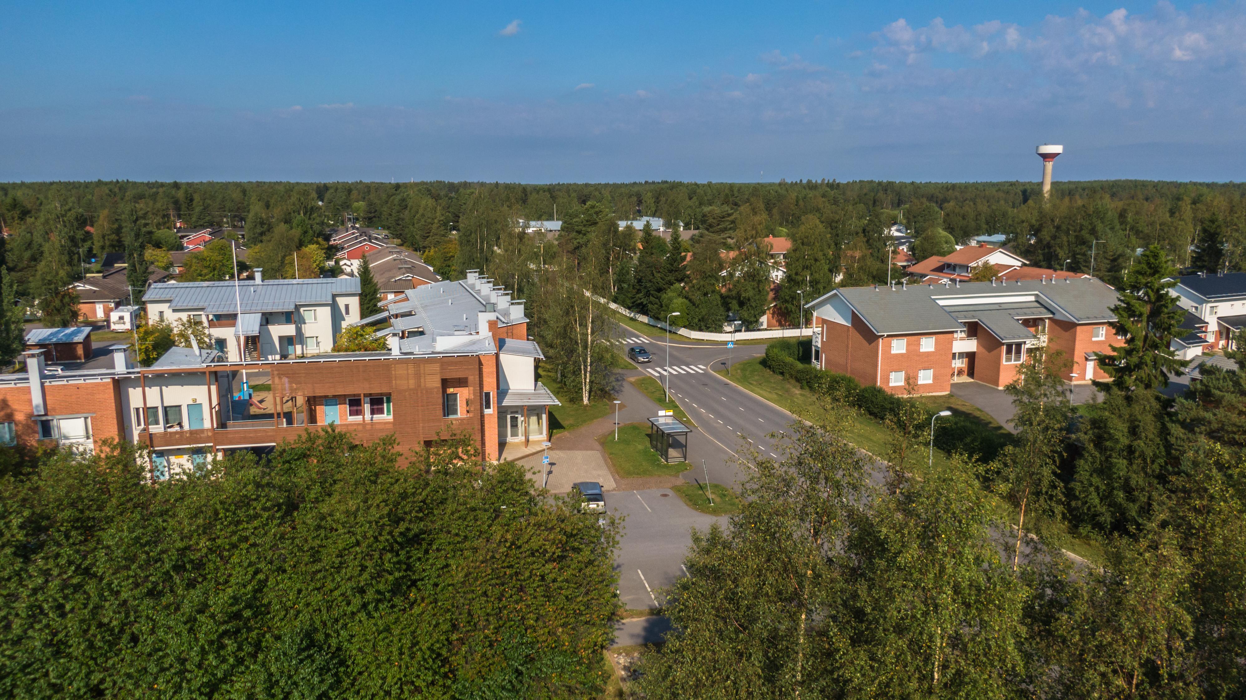 Ilmasta dronella otettu kuva Oulunsalon Pitkäkankaan kerrostalolähiöstä. Metsää, punertavia ja vaaleita taloja. Sininen taivas, jossa poutapilviä.