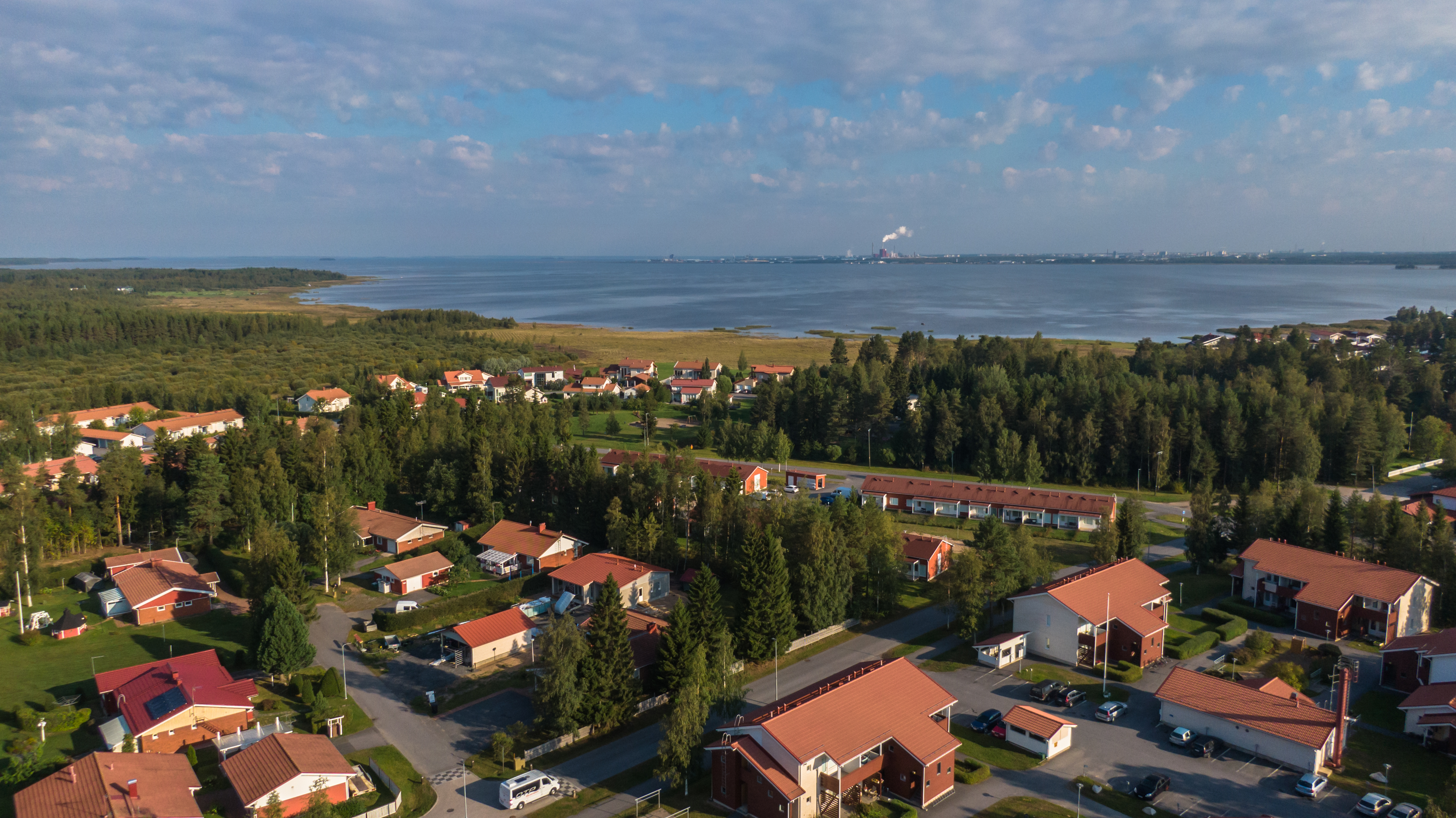 Ilmakuva Oulunsalossa sijaitsevasta Vihiluodon asuinalueesta. Taivaalla pilviä, mutta aurinko paistaa. Metsää ja merenrantaa, etualalla punakattoisia taloja.
