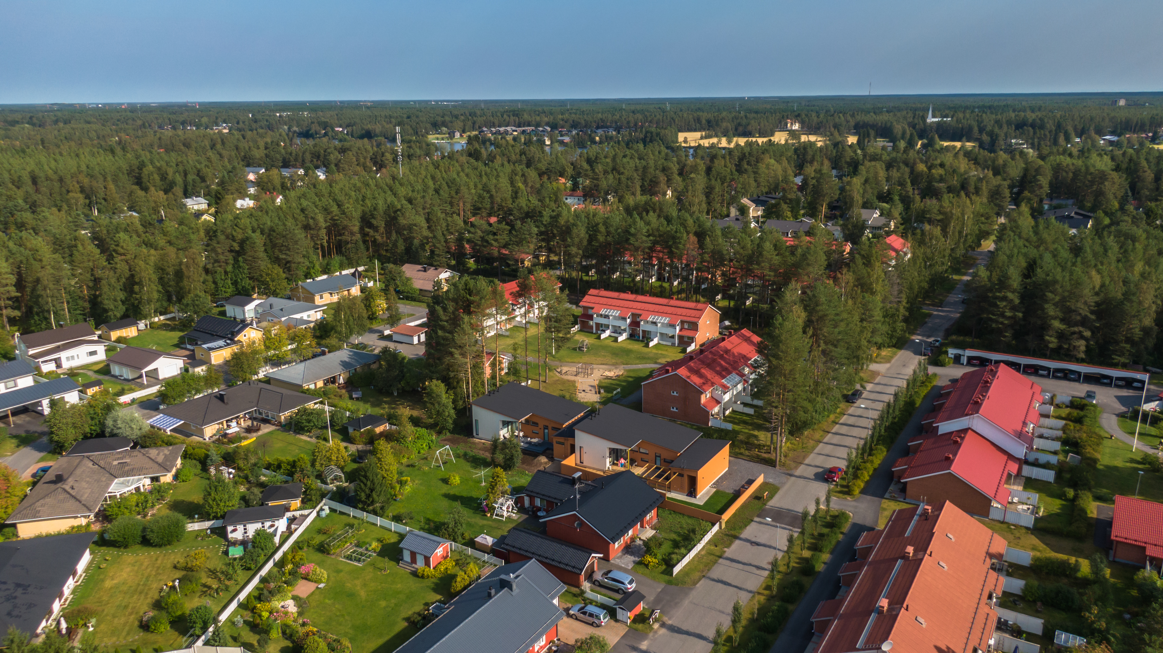 Oulunsuun alueelta Oulusta ilmasta otettu kuva, jossa kaupunkilähiötä ja musta- ja punakattoisia taloja.