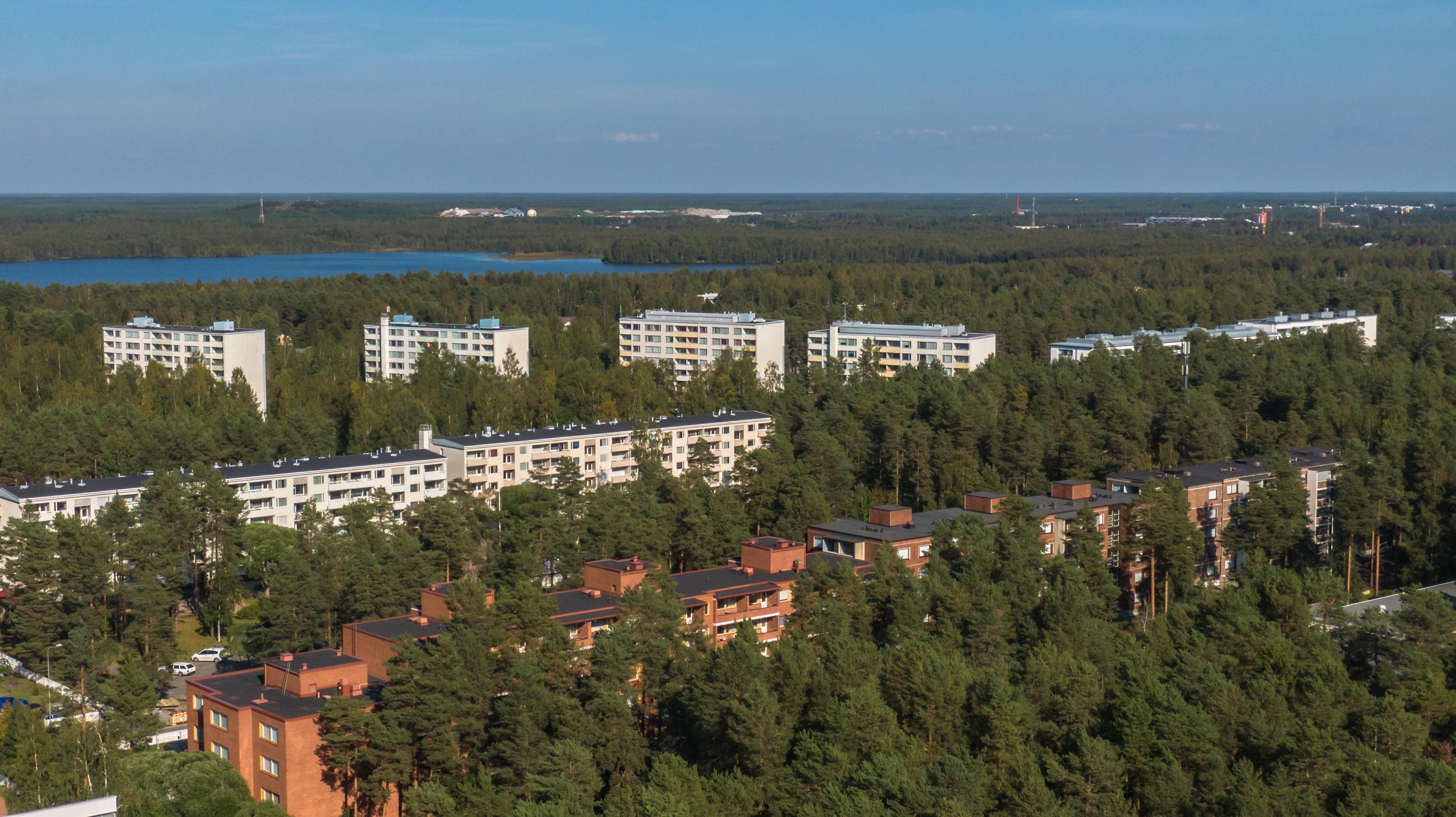 Metsäistä maisemaa Puolivälinkankaalta Oulusta. Valkoisia ja punaisia kerrostaloja puiden ympäröimänä.