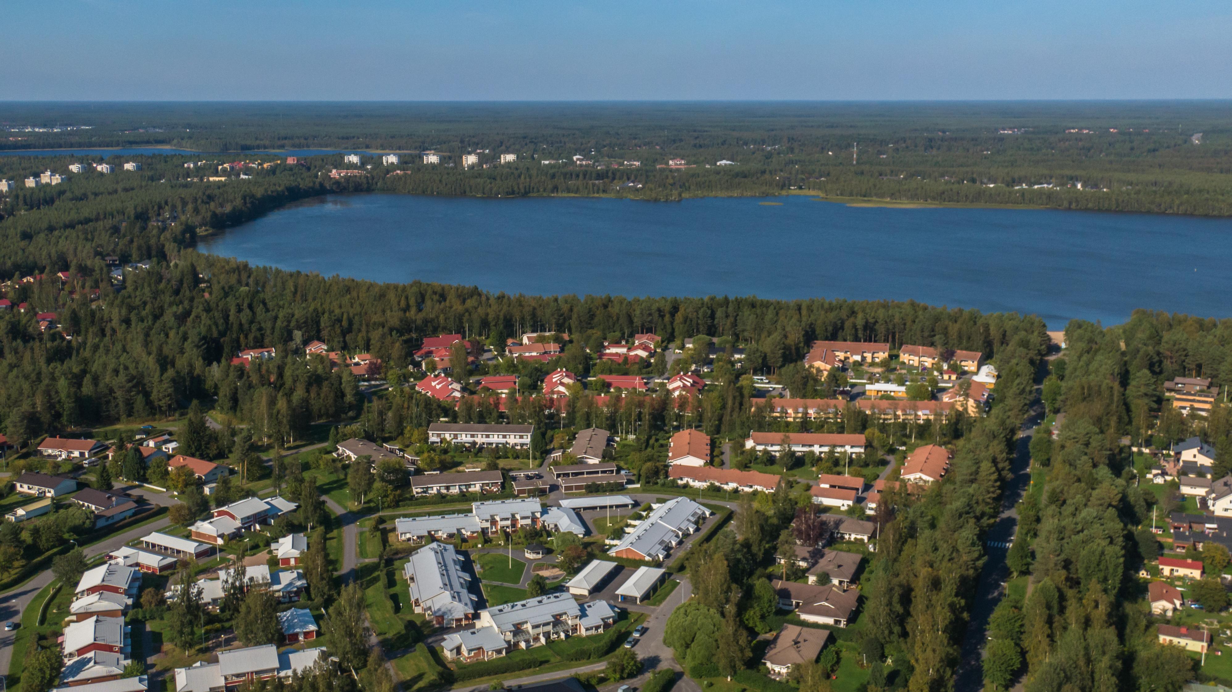 Pyykösjärvi näkyy kesällä otetussa ilmakuvassa Oulun Pyykösjärven asuinalueelta. Metsää ja siistiä omakoti- ja rivitaloasutusta. Harmaa-, ruskea- ja punakattoisia taloja.