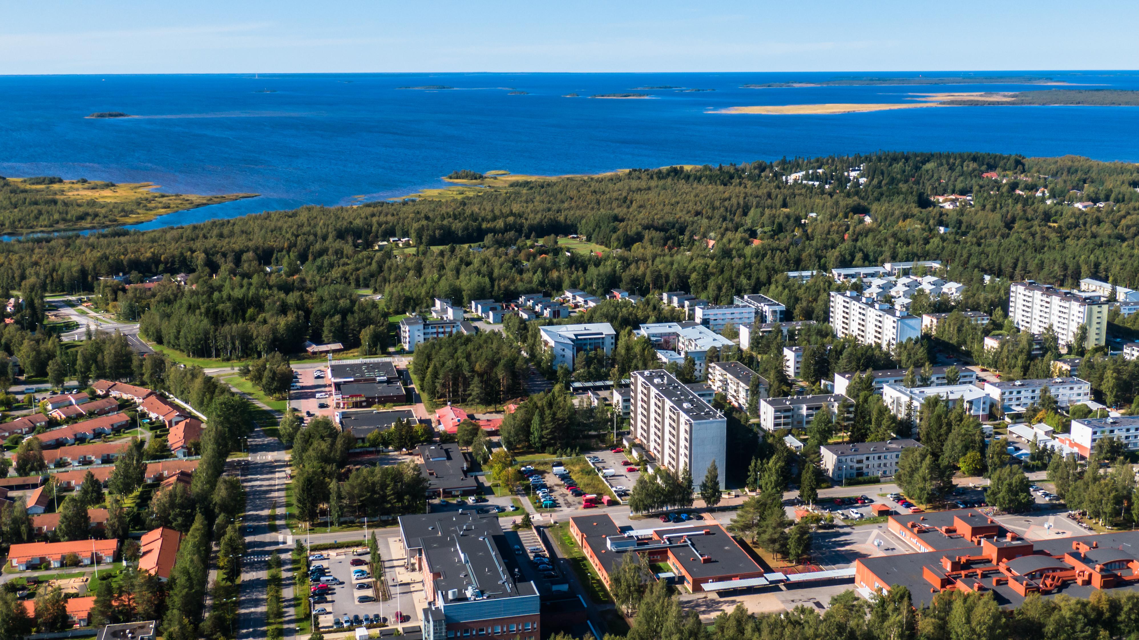 Oulun Rajakylää ilmasta kuvattuna. Punakattoisia taloja ja vaaleita korkeita kerrostaloja. Taaempana näyttäytyy metsää ja meri.
