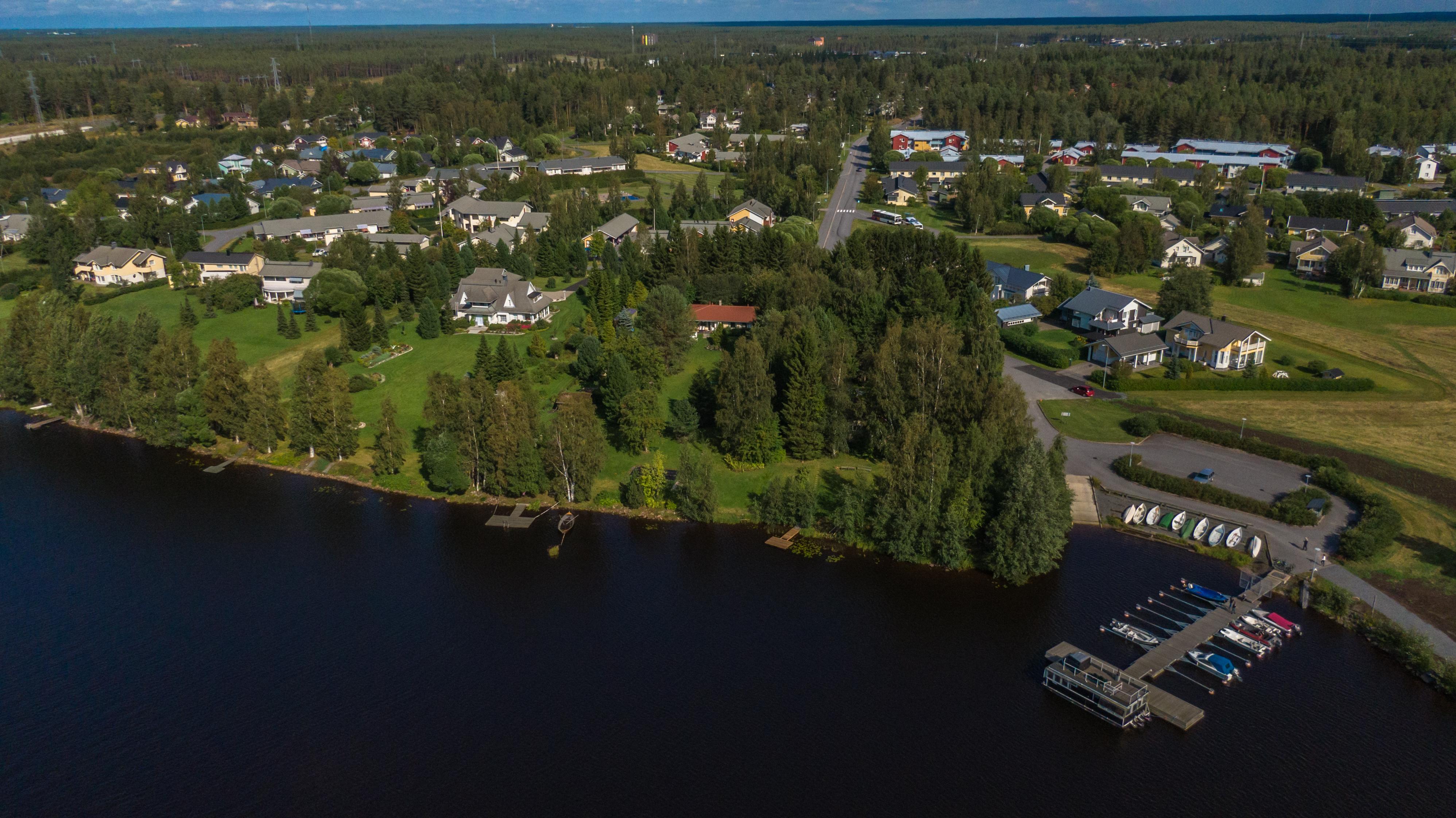 Ilmasta Oulun Saarelassa otettu kuva, jossa näkyy Oulujokea ja ranta-aluetta. Oikeassa alareunassa venelaituri. Monipuolista rakennuskantaa ja taustalla metsämaisemaa.