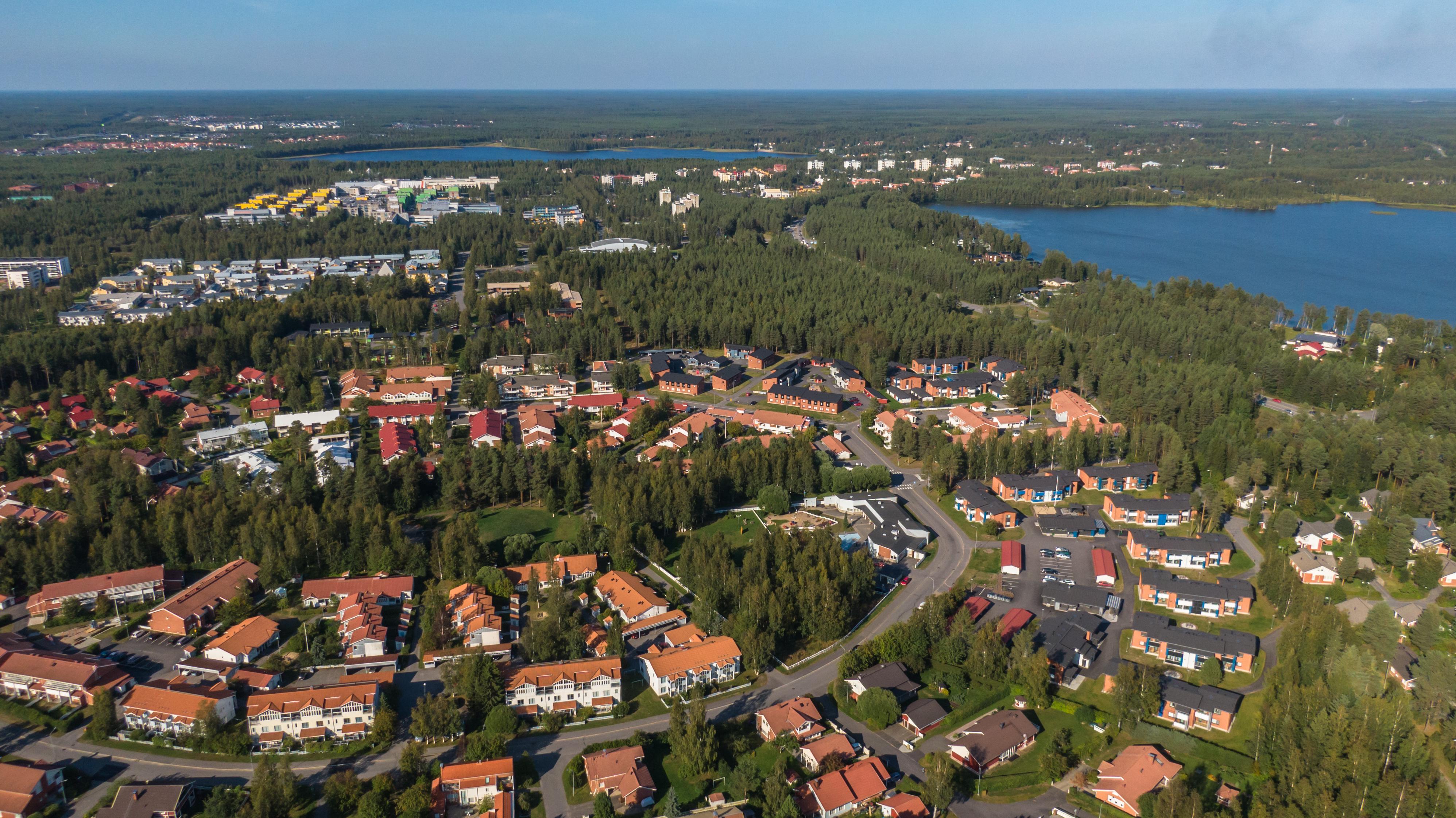 Ilmakuva Oulun Syynimaalta. Punakattoisia luhtitaloja etualalla. Metsäistä asuinaluetta. Kuvan oikeassa reunassa näkyy Pyykösjärvi ja kauempana kuvan yläosassa on Kuivasjärvi. Myös yliopistoaluetta näkyy kuvassa.