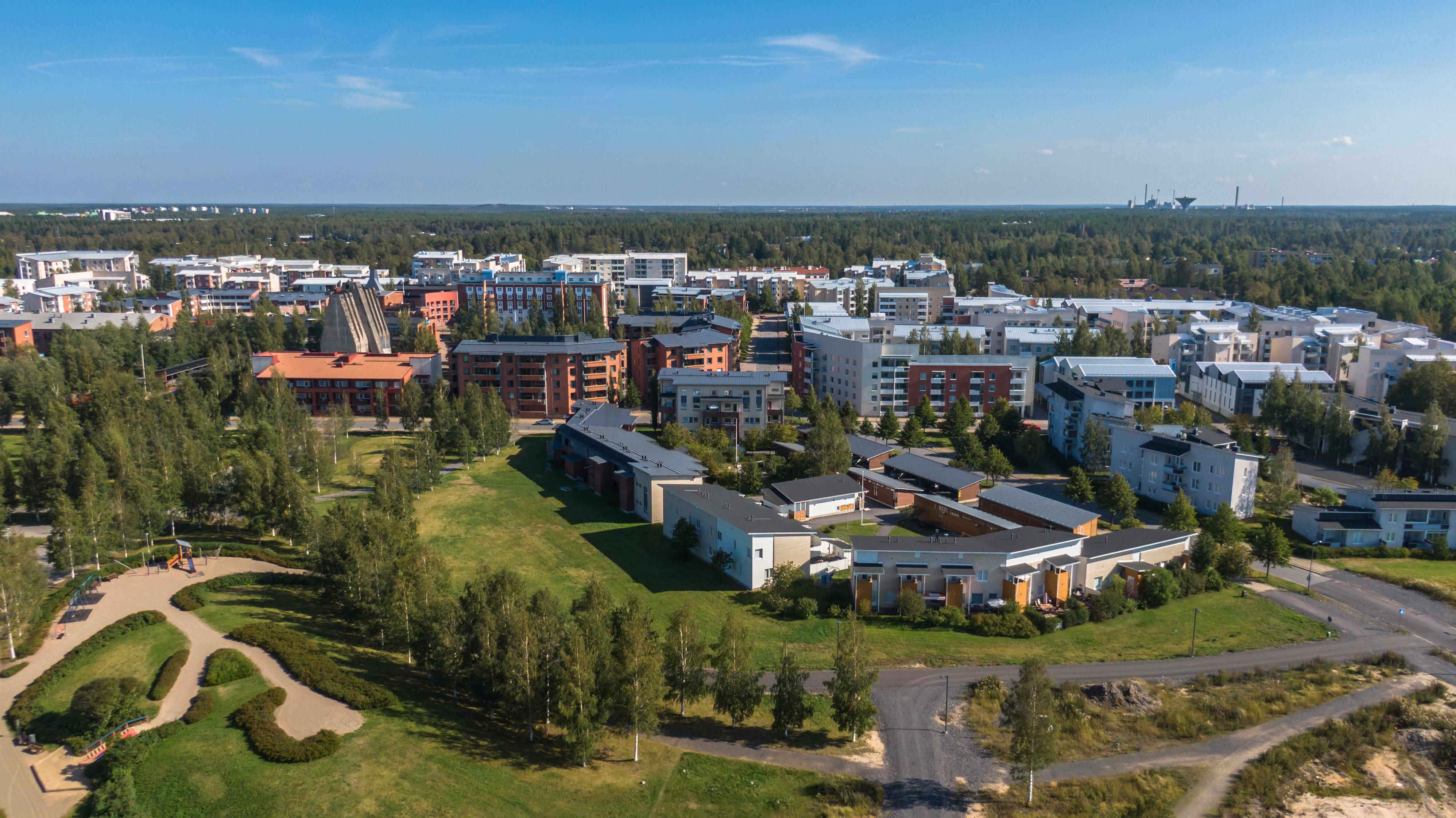Ilmasta dronen avulla otettu kuva Toppilan kaupunginosasta Oulusta. Puistoaluetta ja kerrostaloja.