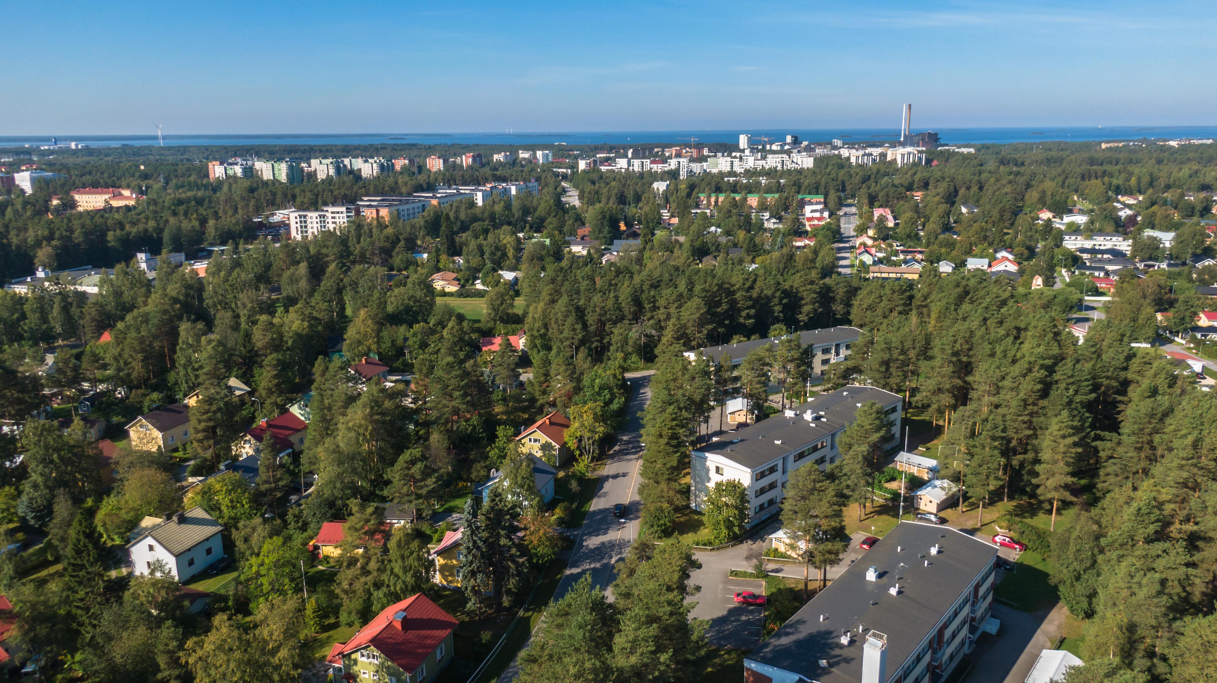 Oulun Välivainiolta ilmassa otetussa kuvassa näkyy puistomaista asuinaluetta, jossa on kerrostaloja ja omakotitaloja. Taustalla meri ja sinertävä taivaanranta.